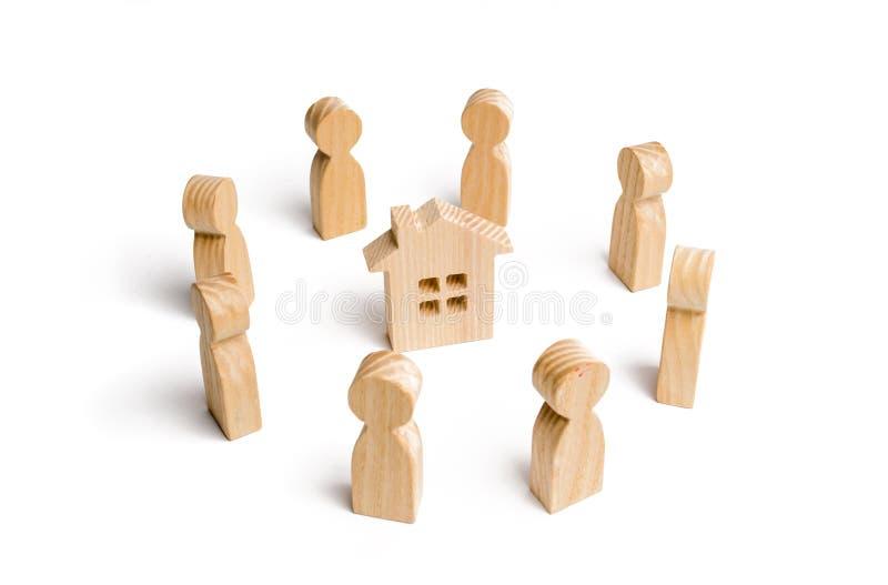 Hölzerne Figürchen des Leutestands um das Haus Suche nach einem neuen Haus und Immobilien Ein Haus kaufen oder verkaufend lizenzfreie stockbilder