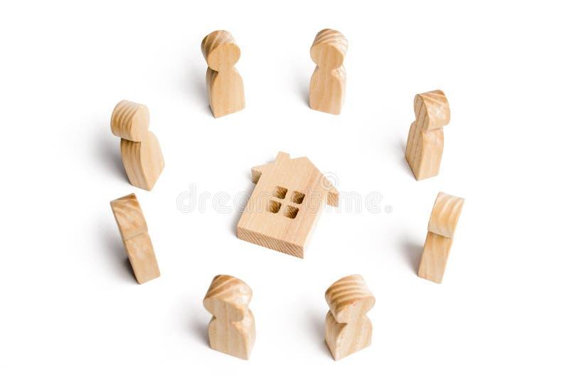 Hölzerne Figürchen des Leutestands um das Haus Suche nach einem neuen Haus und Immobilien Ein Haus kaufen oder verkaufend lizenzfreies stockbild