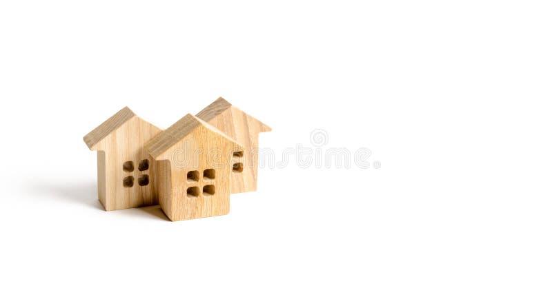 Hölzerne Figürchen von Häusern auf einem weißen Hintergrund Minimalismus- und Kopienraum Investitionen in den Häusern und in den  lizenzfreies stockbild
