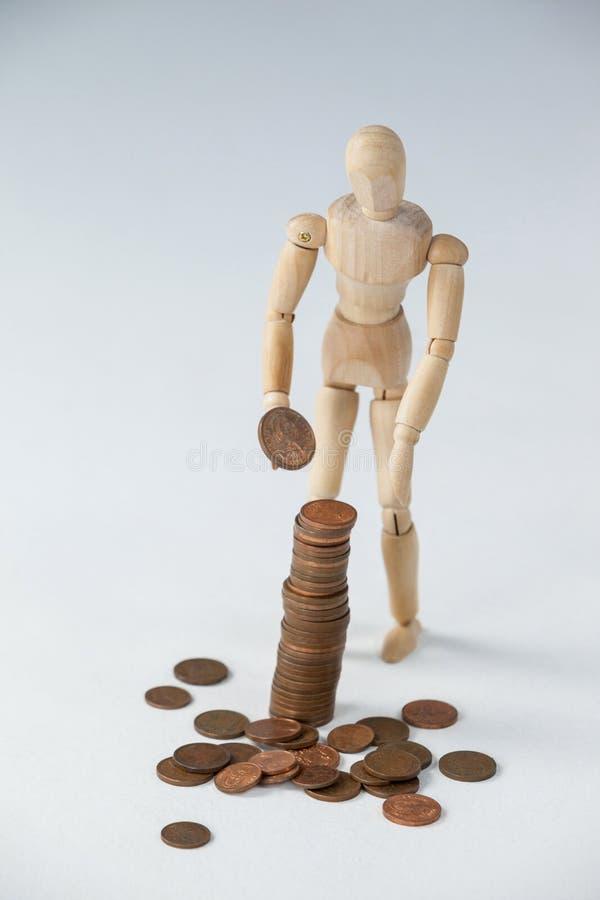 Hölzerne Figürchenstellung und Herstellungsstapel Münzen lizenzfreie stockbilder