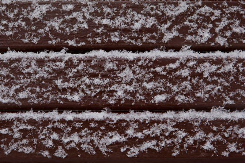 Hölzerne gemalte Bretter umfasst mit Schnee stockfoto