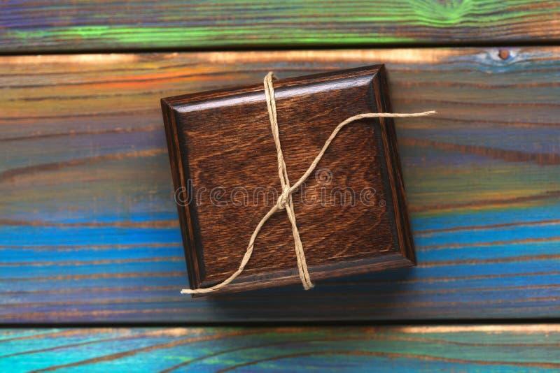 Hölzerne Geschenkbox auf mehrfarbigem strukturiertem Hintergrund Schmuckkästchen gebunden mit einem Seil stockbilder