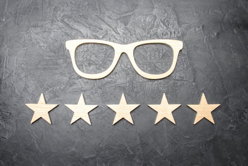 Hölzerne Gläser und fünf Sterne auf einem konkreten Hintergrund Gläser der hohen Qualität Die beste Optik Korrektur der Vision lizenzfreies stockfoto