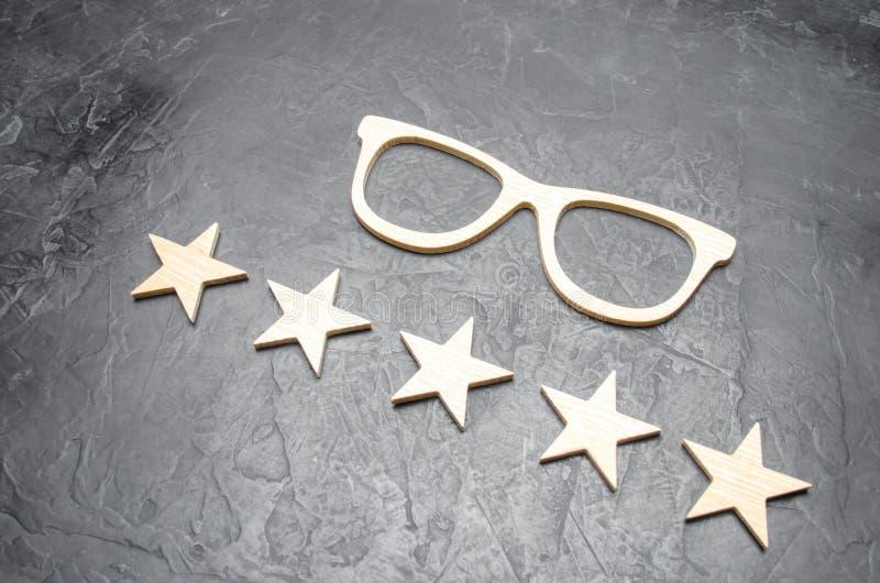 Hölzerne Gläser und fünf Sterne auf einem konkreten Hintergrund Gläser der hohen Qualität Die beste Optik Korrektur der Vision lizenzfreie stockbilder