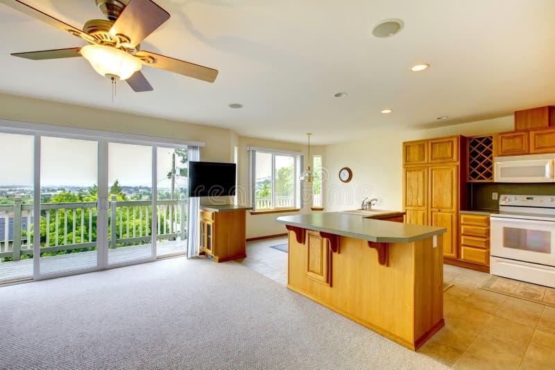 Hölzerne goldene Küche mit Esszimmer, Fernsehen und vielen Fenstern zum Balkon stockbilder