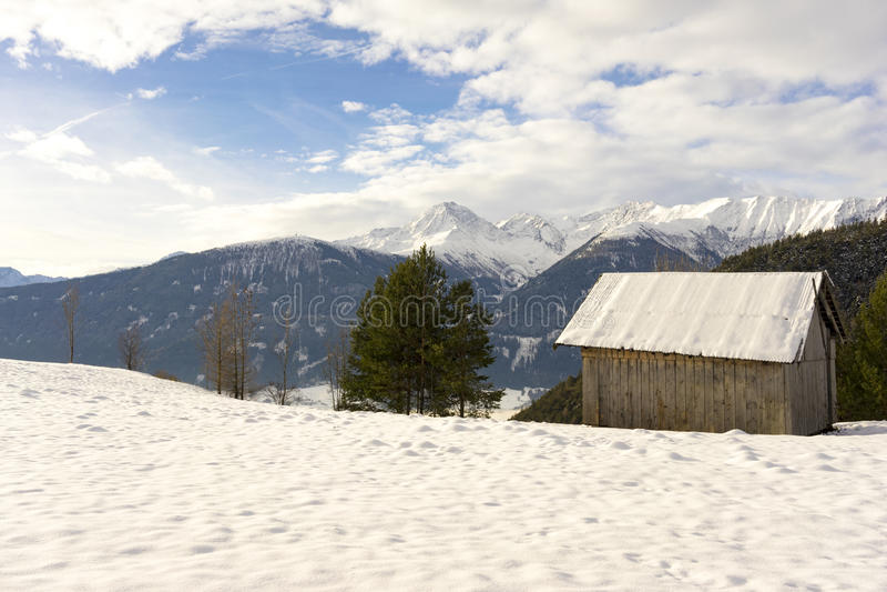 Hölzerne Hütte im Gebirgsschnee stockfoto