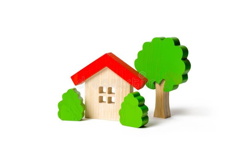 Hölzerne Hütten- und Baumfigürchen mit Büschen auf einem lokalisierten Hintergrund Das Konzept eines Liebesnest Landzustandes dat lizenzfreies stockfoto