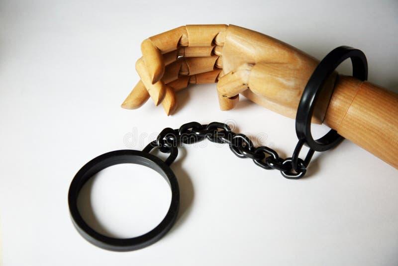 Hölzerne Hand in den Handschellen stockbilder