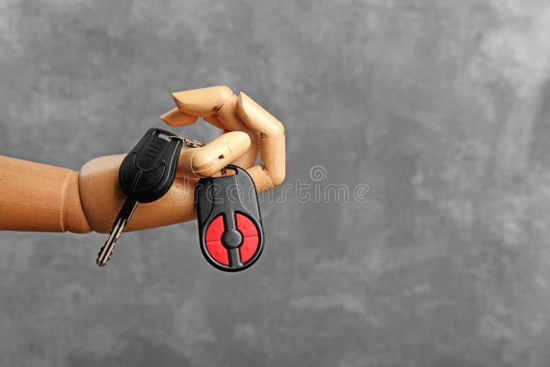 Hölzerne Hand, die Autoschlüssel hält lizenzfreie stockfotografie