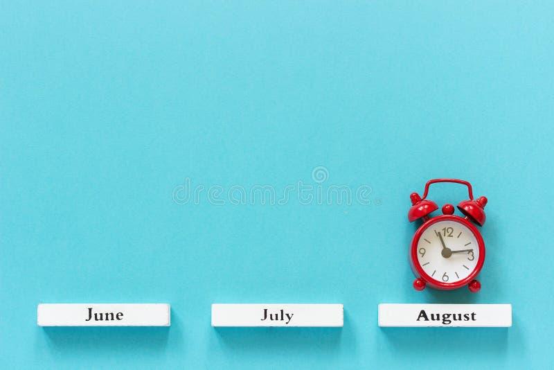 Hölzerne Kalendersommermonate und roter Wecker in August auf blauem Hintergrund Kreative Draufsicht Konzept-August-Zeit flache La lizenzfreie stockfotos