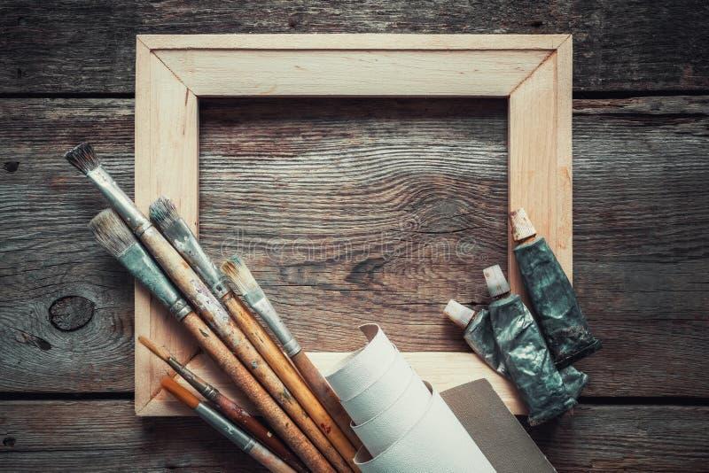 Hölzerne Keilrahmenleiste, Malerpinsel, Rolle des Künstlersegeltuches und Farbenrohre stockfotos