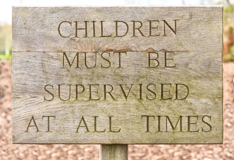 Hölzerne Kinder müssen überwachtes Zeichen sein stockfoto