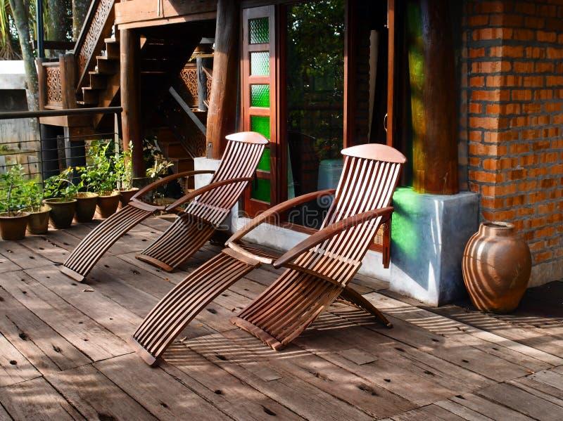 Hölzerne Kippstühle auf Patio lizenzfreie stockbilder