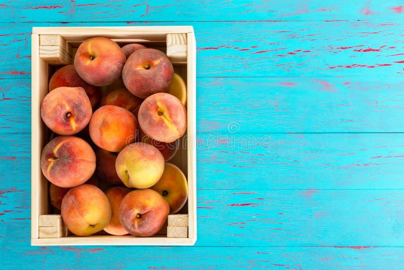 Hölzerne Kiste gefüllt mit reifen saftigen Pfirsichen lizenzfreie stockfotos