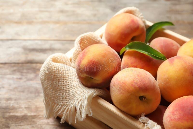 Hölzerne Kiste mit frischen süßen Pfirsichen auf Tabelle stockbilder