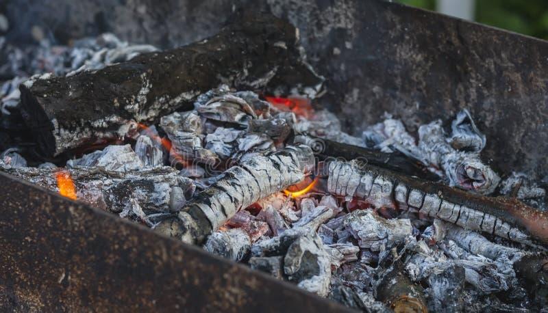 Hölzerne Kohlen mit einer Flamme in einem mongolischen bbq lizenzfreies stockbild