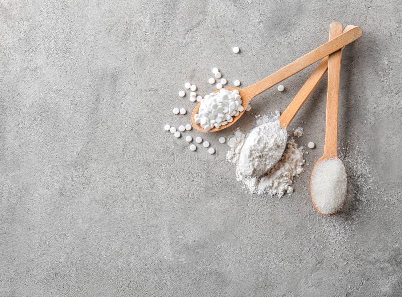 Hölzerne Löffel mit Steviapillen-, pulverisiertem und raffiniertemzucker auf grauer Tabelle stockfoto