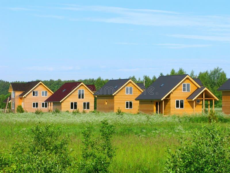 Hölzerne Landhäuser auf grünem Feld, eco Bau lizenzfreies stockbild
