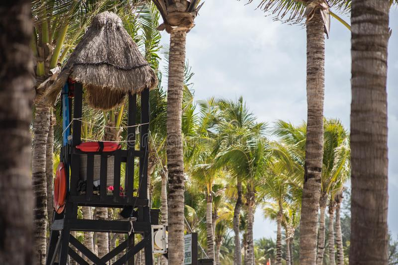 Hölzerne Lebenschutzhütte auf tropischem Strand mit Palmen an einem sonnigen Tag lizenzfreies stockbild