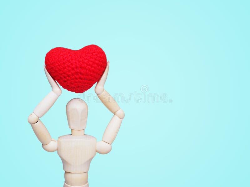 Hölzerne Mannzahl, die Herzform hält stockbilder