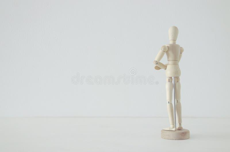 hölzerne Person, welche mit seiner die Rückseite betrachtet leeres Leerraumkonzept steht stockfotografie
