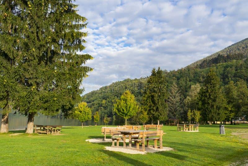 Hölzerne Picknicktische auf Rasenfläche, entlang See Levico Terme, Italien stockfotografie