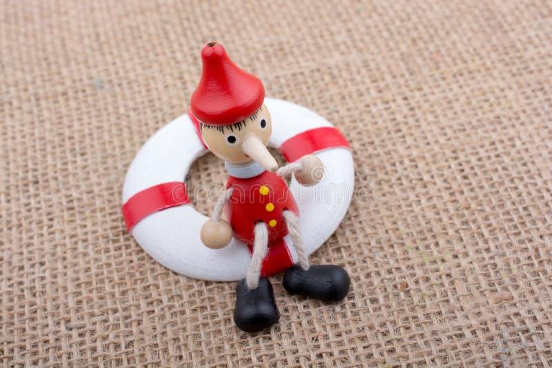 Hölzerne Pinocchio-Puppe gebunden an einem Lebensretter stockbild