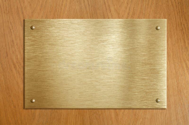 Hölzerne Plakette mit Gold oder Messingplatte lizenzfreie stockfotografie