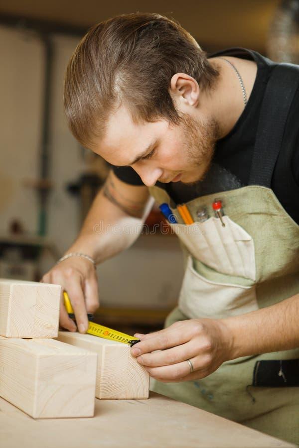 Hölzerne Planken des Handwerkermaßes mit Machthaber Tischler an der Werkstatt lizenzfreies stockbild
