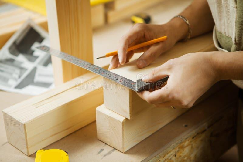 Hölzerne Planken des Handwerkermaßes mithilfe des Machthabers Tischlerswerkstatt stockbild