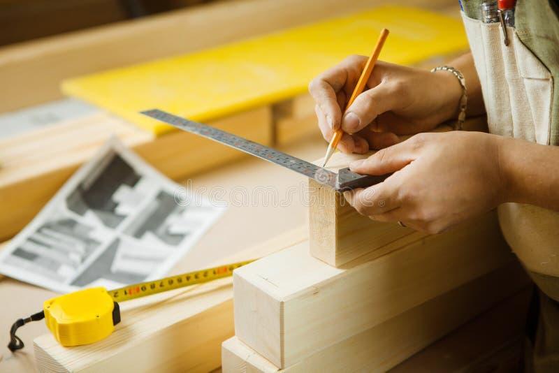 Hölzerne Planken des Handwerkermaßes mithilfe des Machthabers Tischlerswerkstatt lizenzfreie stockfotos