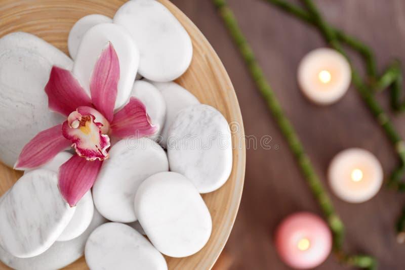 H?lzerne Platte mit Badekurortsteinen und Orchideenblume auf unscharfem Hintergrund stockfoto