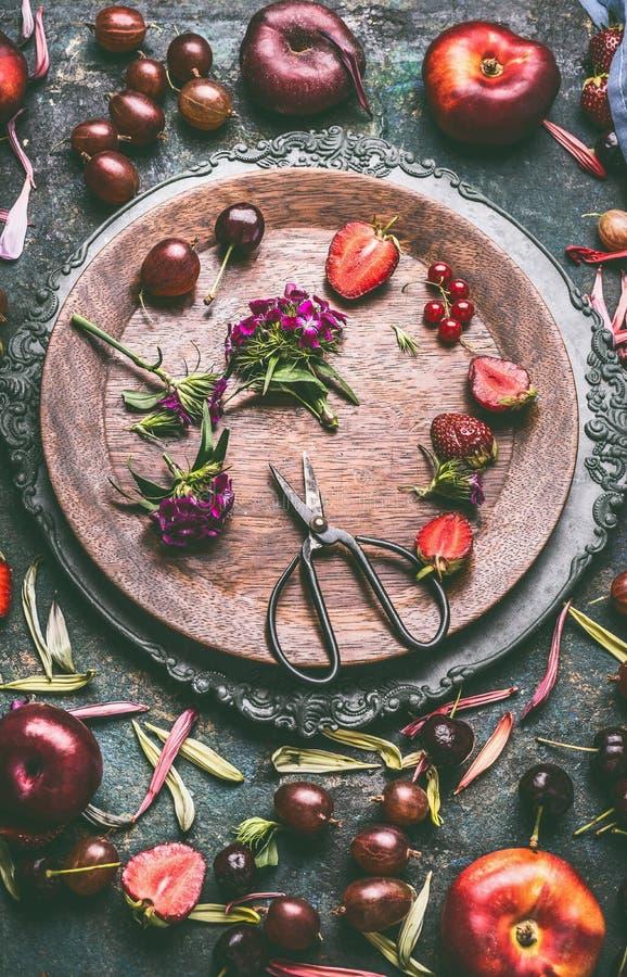 Hölzerne Platte mit Saisonfrüchten, Beeren, Blumen und Scheren auf rustikalem Küchentischhintergrund stockfotografie