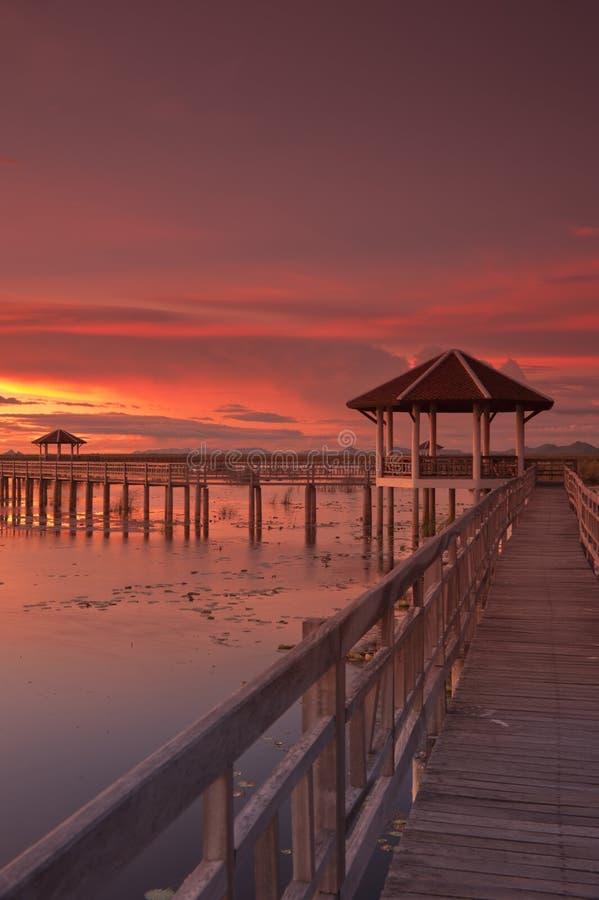 Hölzerne Promenade am Sonnenuntergang. lizenzfreie stockbilder