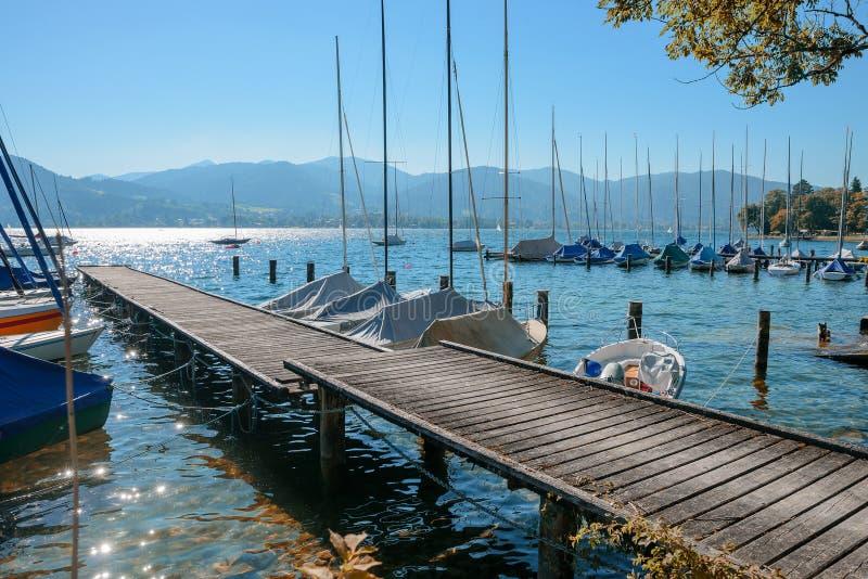 Hölzerne Promenade und festgemachte Segelboote an See tegernsee lizenzfreies stockbild