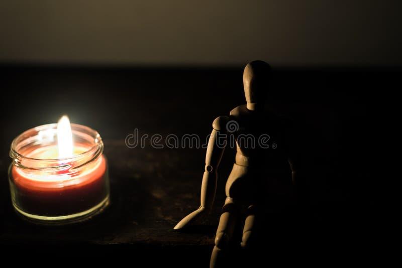 Hölzerne Puppe auf einem schwarzen Hintergrund angesichts einer Kerze in einem Glas lizenzfreie stockfotografie