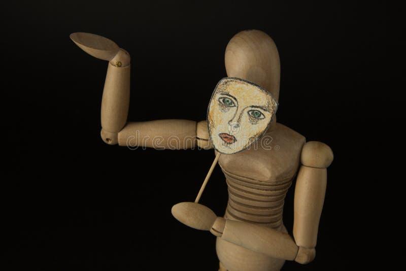 Hölzerne Puppe auf Scharnieren hält eine Maske in den Händen und bedeckt ihr Gesicht lizenzfreie stockbilder