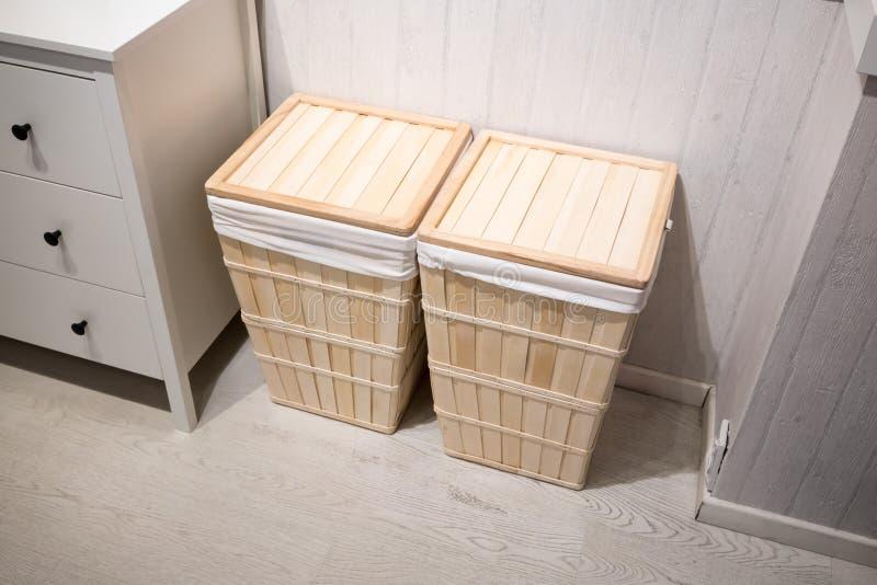 Hölzerne quadratische Wäschekörbe mit dem Leinen, das gegen Weiß steht stockfotografie