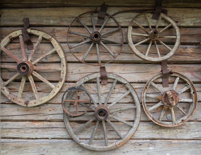 Hölzerne Räder von einem alten Wagen, der an der Wand hängt lizenzfreie stockfotografie