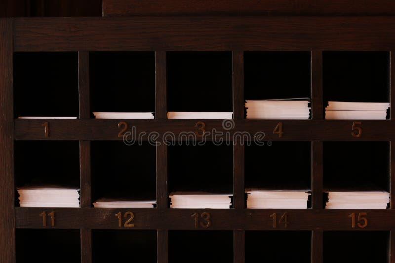 Hölzerne Regalschlitze für Papier stockfotos