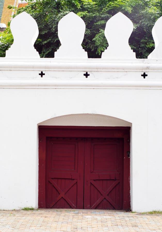 Hölzerne rotbraune Tortür des geschlossenen kleinen Ausganges auf der starken Mauer des THAILÄNDISCHEN GROSSARTIGEN PALASTES stockbilder