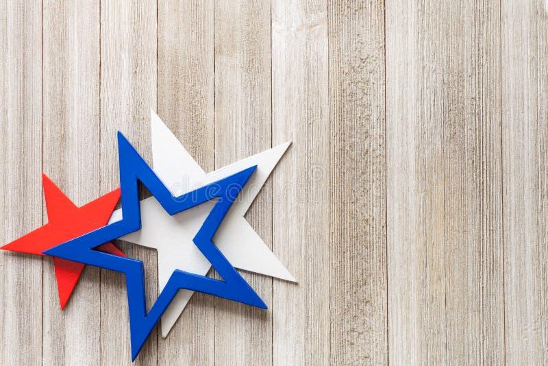 Hölzerne rote, weiße und blaue Sterne auf einem rustikalen Hintergrund mit Kopie sperren,/4. des Juli-Hintergrundkonzeptes lizenzfreies stockbild