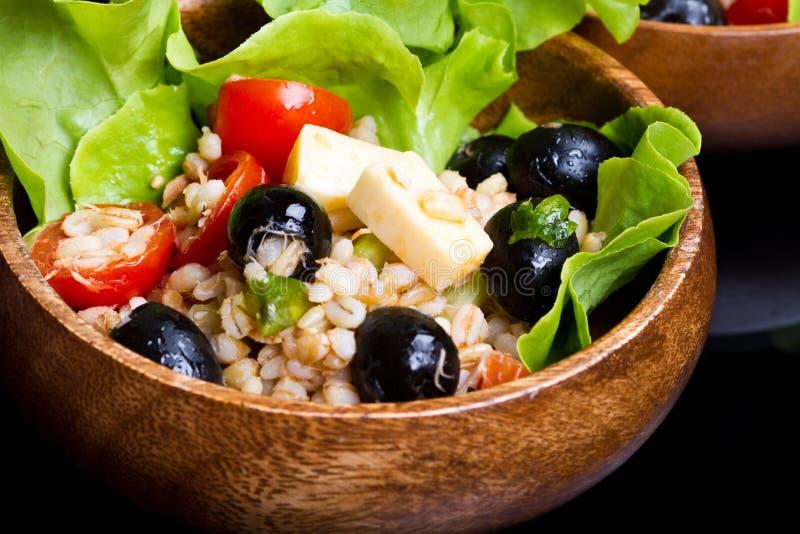 Hölzerne Schüssel mit buchstabiertem Salat mit Oliven und Tomaten stockfotos