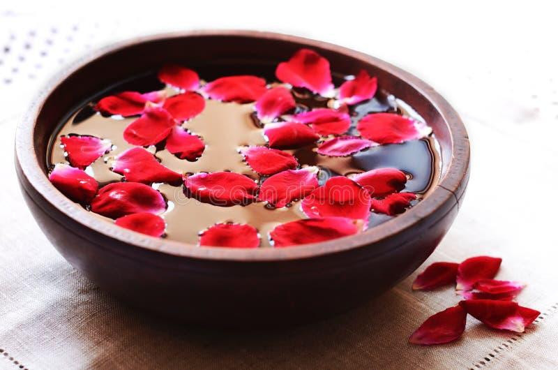 Hölzerne Schüssel mit dem Schwimmen von roten rosafarbenen Blumenblättern lizenzfreie stockbilder