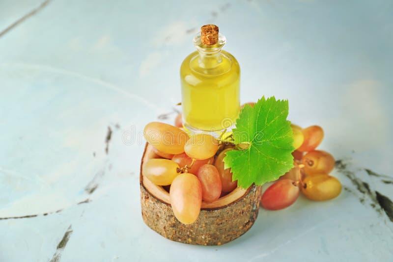 Hölzerne Schüssel mit frischen Trauben und Flasche Öl auf Tabelle stockfotos
