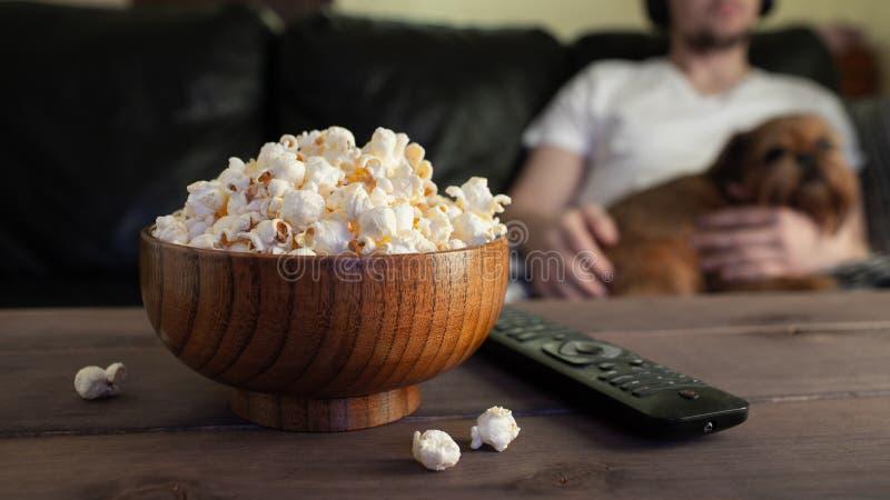 Hölzerne Schüssel mit gesalzenem Popcorn und Fernsehen entfernt auf Holztisch Im Hintergrund ein Mann mit einem roten Hund, der a lizenzfreie stockfotos