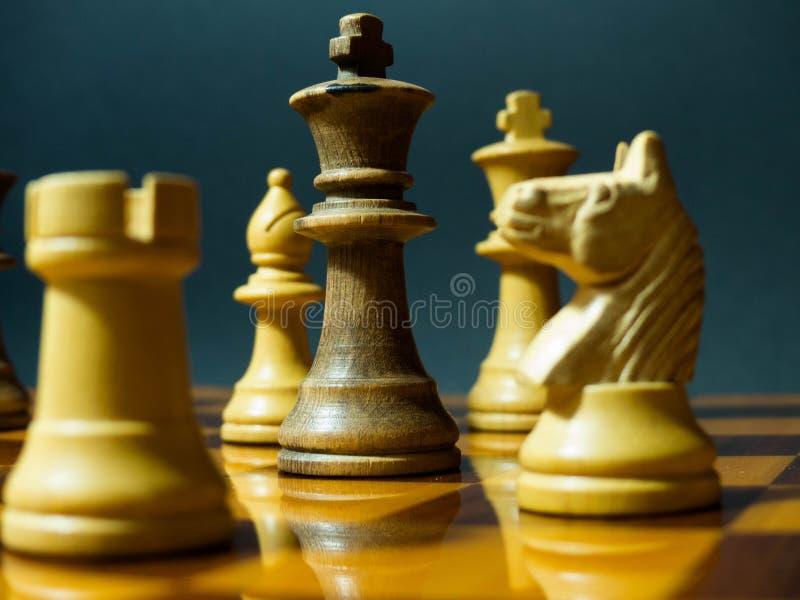 Hölzerne Schachfiguren auf einem hölzernen Schachbrett lizenzfreies stockfoto