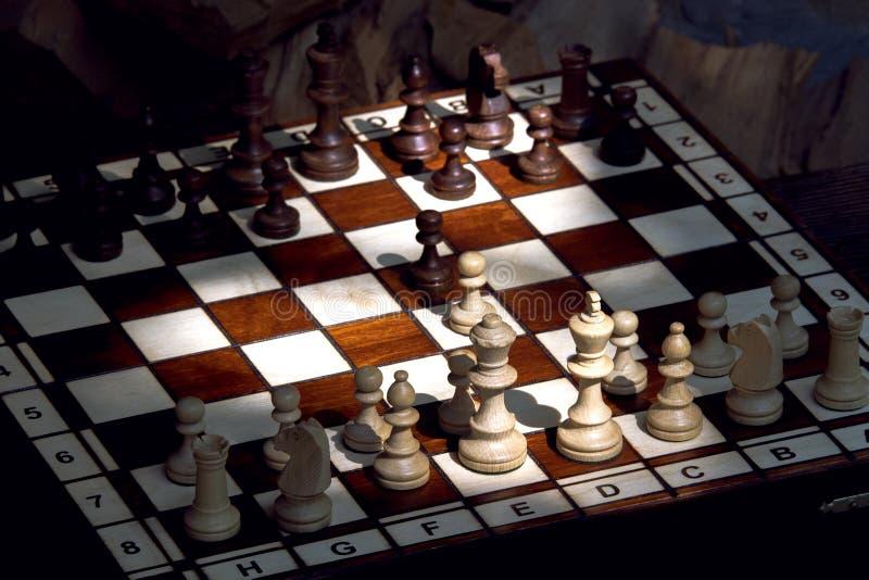 Hölzerne Schachfiguren auf einem hölzernen Schachbrett im Freien am sonnigen stockbilder