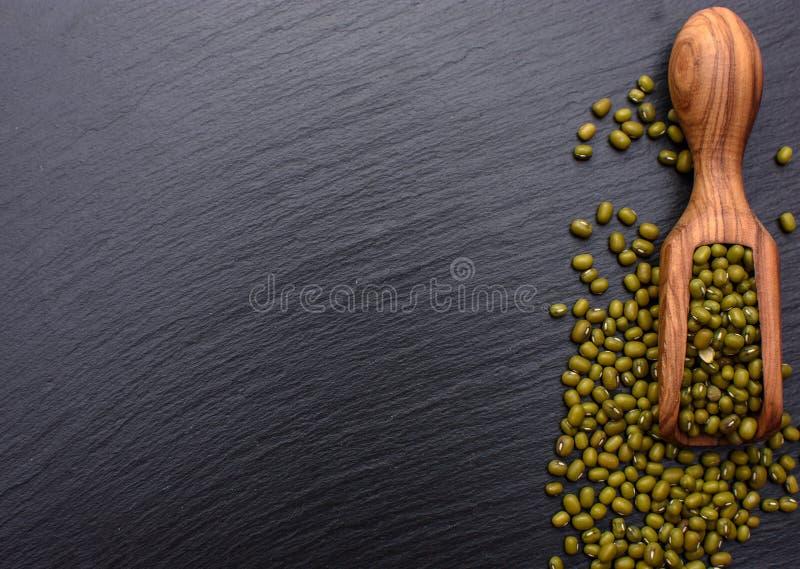 Hölzerne Schaufel der Bohnen auf dem Hintergrund eines schwarzen Steinbrettes, Platz für Text, Mungobohne lizenzfreie stockfotos