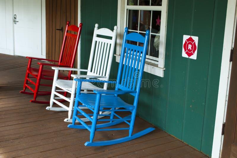 3 hölzerne Schaukelstühle im Freien in der roten, weißen und blauen Farbe lizenzfreie stockfotos